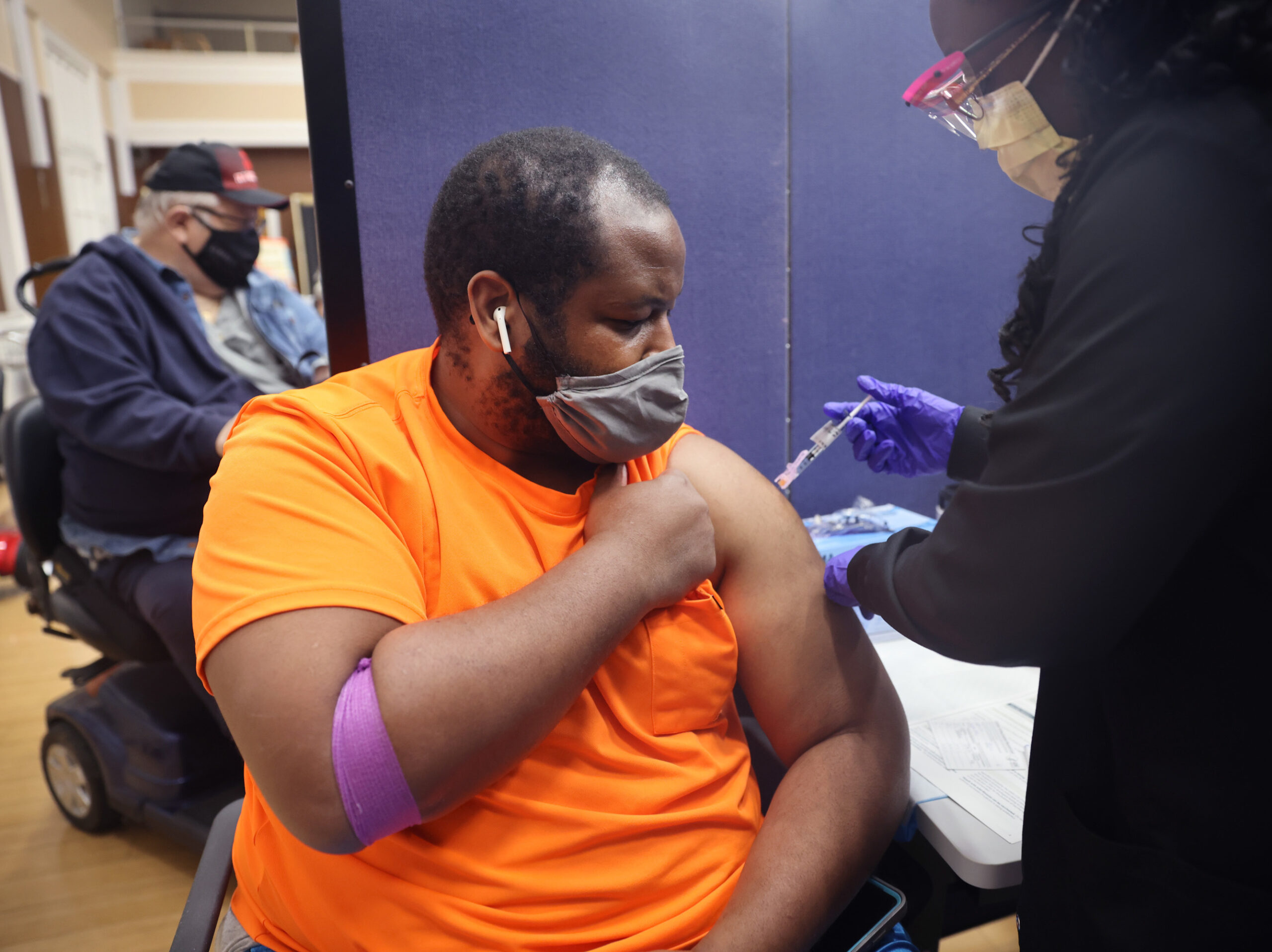 A man in an orange shirt lifts up his sleeve to get a shot.